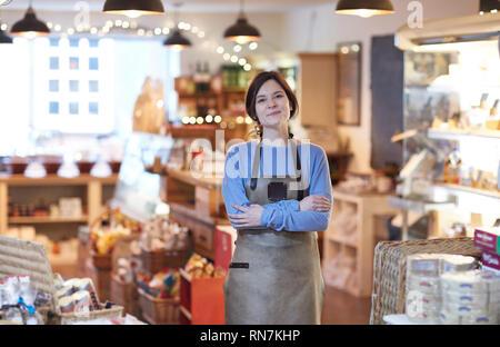 Portrait Of Smiling Female Owner Of Delicatessen Shop Wearing Apron - Stock Image
