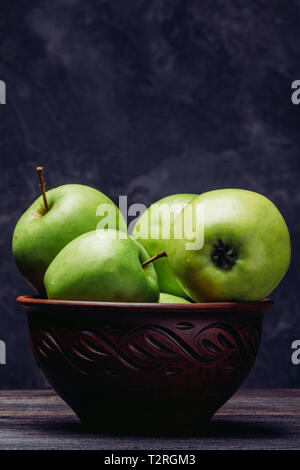 Green apples ripe on a concrete background in a clay bowl - Stock Image