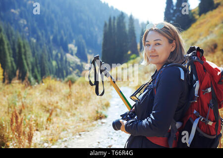 Portrait confident young female photographer backpacking on sunny trail - Stock Image