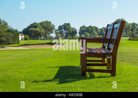Wooden bench on a sunny day in golf course - Stock Image