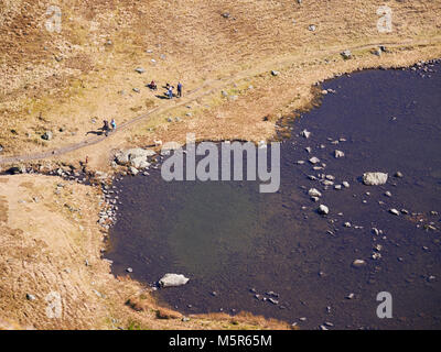 Aerial view of Bowscale Tarn with hikers, walkers relaxing beside it in the English Lake District, UK. - Stock Image