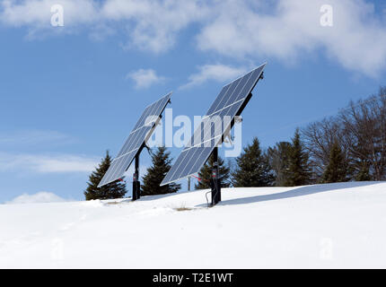 Free standing pole mounted residential Solar photovoltaic panels on a hilltop in a winter rural setting. - Stock Image