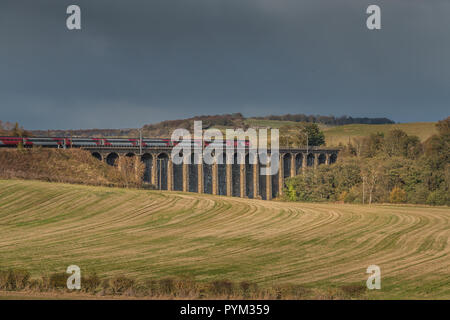 A northbound LNER train crossing Alnmouth Viaduct with winter sunshine and a dark sky background - Stock Image