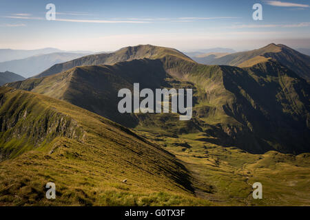 Mountainside with green grass, valley and peaks with blue sky in a background, Carpathian Mountains in Romania - Stock Image