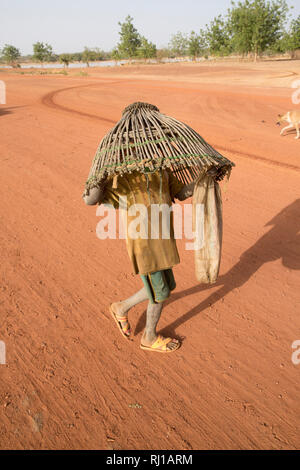Samba village, Yako Province, Burkina Faso: A young boy carryng a fishing basket to catch fish in the lake on one of the days when fishing is allowed. - Stock Image