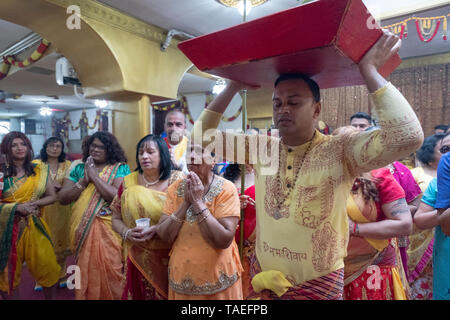 At his mother's thanksgiving service a young Hindu man brings offerings to the deities at a temple in Ozone Park, Queens, New York City. - Stock Image