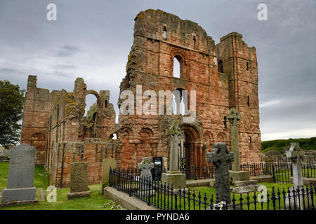 Front of Lindisfarne church ruins of the medieval priory with rainbow arch and cemetery tombstones on Holy Island of Lindisfarne England UK - Stock Image
