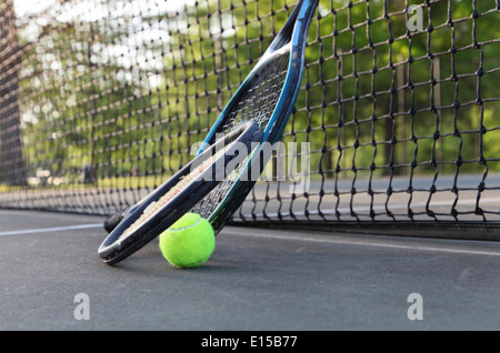 Tennis rackets, ball leaning against net. - Stock Image