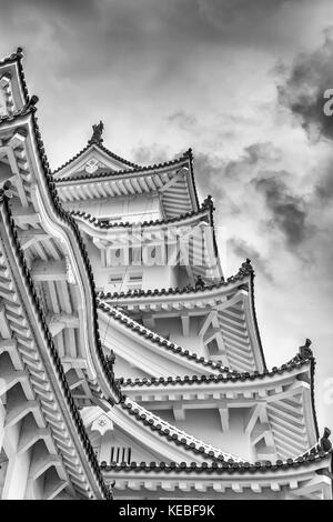 The roof detailing of Himeji Castle, one of Japan's UNESCO world heritage sites against a stormy sky - Stock Image