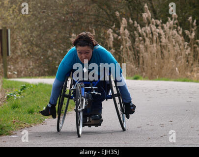 wheelchair athlete training along the Exeter Canal cycle path, Devon, UK - Stock Image