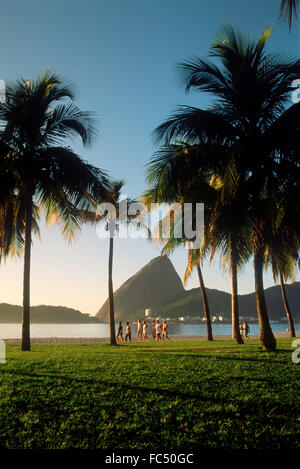 People taking morning jog and walk along Flamengo Beach near Sugar Loaf at sunrise in Rio de Janeiro Brazil - Stock Image