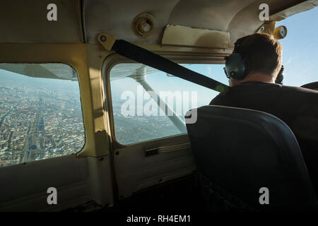 Man flying small airplane over city - Stock Image