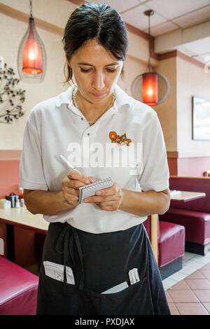 Miami Coral Gables Miami Florida Bagel Emporium and Grille restaurant deli woman waitress take order job employment apron business wri - Stock Image