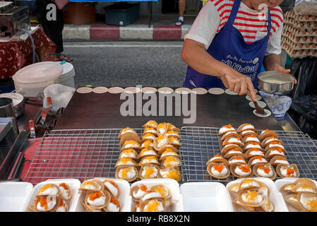 Thailand street food vendor preparing a popular Thailand sweet known as Khanom Bueang at her street food stall. - Stock Image