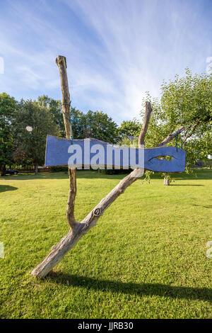 Blue sign made of wood with green grass and blue sky in background - Stock Image