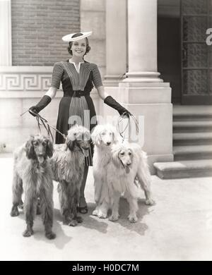 A woman and her four Afghan Hounds - Stock Image