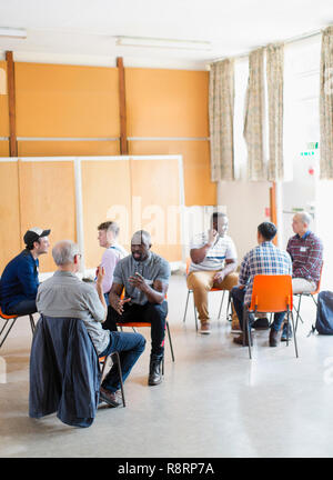 Men talking in group therapy in community center - Stock Image
