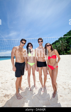 Friends posing on a beach. - Stock Image
