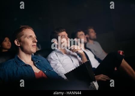 Group of people sitting in multiplex movie theater. Young friends watching movie in cinema hall. - Stock Image