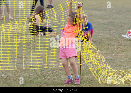 Small girl struggling or perhaps with yellow plastic netting - Stock Image