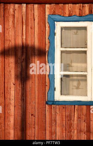 Shadow from a street lamp on a wooden painted wall with a white window and lace curtains on a sunny day - Stock Image