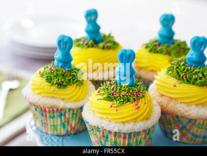 Vanilla cupcakes with yellow buttercream decorated for Easter - Stock Image