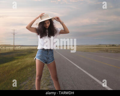Woman in hat standing on highway in countryside - Stock Image
