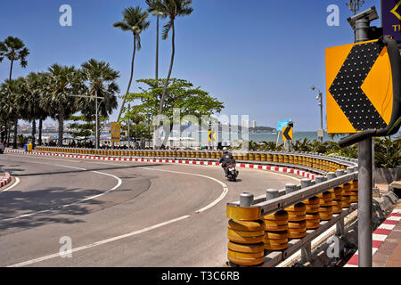 Motorcyclist navigating a sweeping bend with crash barriers protection, Pattaya, Thailand, Southeast Asia - Stock Image
