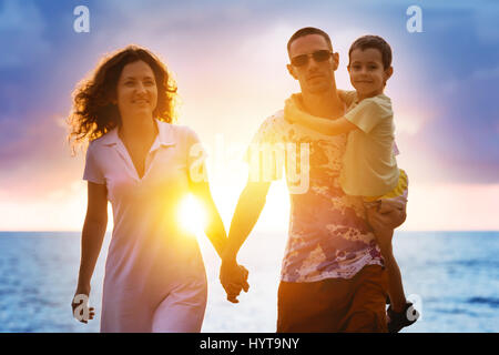 Happy family walking at sunset beach - Stock Image