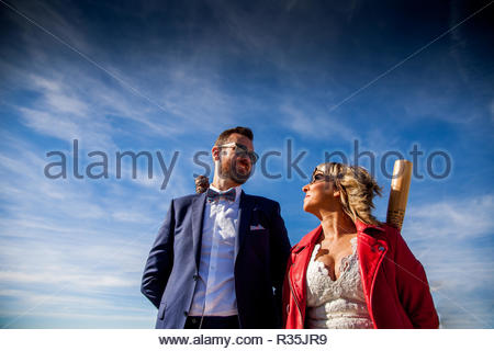 Newlywed couple hold baseball bats while strolling in an outdoor location - Stock Image