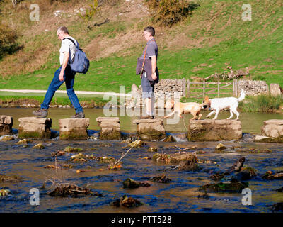 Peak District National Park, Derbyshire, UK. 10th October, 2018. UK Weather two men & two dogs crossing the stepping stones on an unusually hot sunny October day in the tourist hotspot of Dovedale in the Peak District National Park, Derbyshire Credit: Doug Blane/Alamy Live News - Stock Image