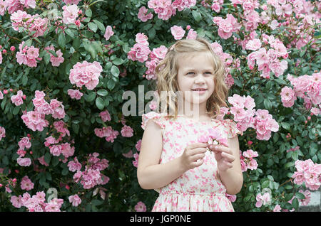 Girl in pink dress with roses - Stock Image