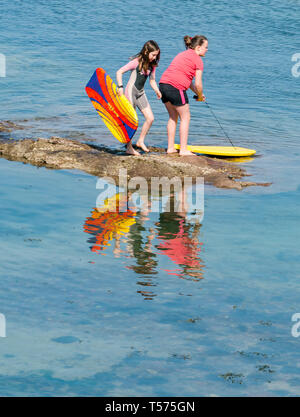 Dunbar, East Lothian, Scotland, UK. 21st Apr 2019. UK Weather: People enjoy the very sunny hot Easter day weather at Eye Cave cove. Girls with surf boards reflected in the sea water - Stock Image