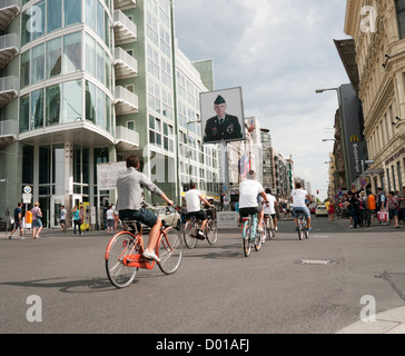 Cyclists ride past Checkpoint Charlie the former border crossing between east and west Berlin Germany - Stock Image