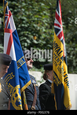 Portsmouth, UK. 15th Aug, 2015. A standard bearer is bathed in sunlight during the VJ Day 70 memorial in Portsmouth. - Stock Image