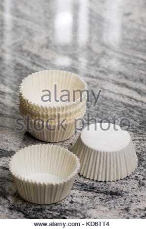 Empty white cup cake cases containers on the grey granite marble background. - Stock Image