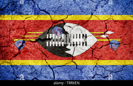 Kingdom of Eswatini or Swaziland flag on dry earth ground texture background - Stock Image