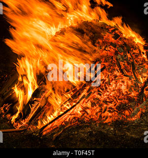 A bonfire at night with charred wood, embers and large flames. - Stock Image