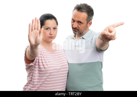 Unhappy man and woman couple making stop gesture with palm or index finger as forbidden concept isolated on white - Stock Image