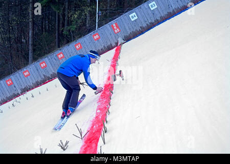 Ski jumping hill. A man is marking the red line of 'critical point' or 'construction point' where - Stock Image