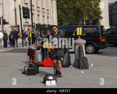 A busker performs on a london street - Stock Image