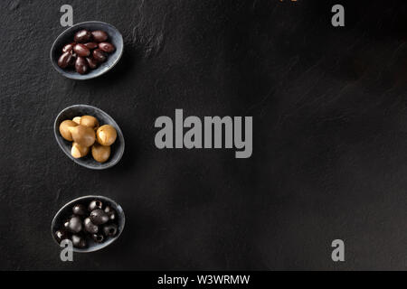 Various types of olives in bowls, overhead shot on a black background with copy space. Purple, green almond stuffed, and black pitted olives - Stock Image