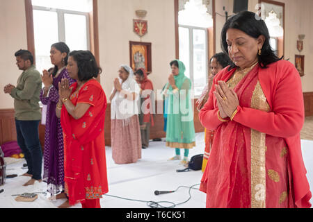 Women in a Hindu temple pray & meditate with their eyes closed and hands clasped. At a temple in Jamaica, Queens, New York City. - Stock Image