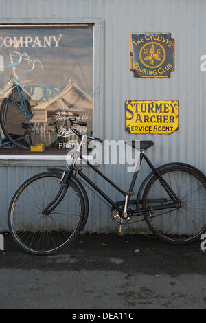 Chichester, West Sussex, UK. 14th Sep, 2013. Goodwood Revival. Goodwood Racing Circuit, West Sussex - Saturday 14th September. A vintage black bicycle leans up against a cycle shop part of the vintage retail area. Credit:  MeonStock/Alamy Live News - Stock Image