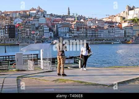 Tourist photographing woman on the Cais de Gaia by River Douro with cityscape in the background in Porto Portugal Europe EU  KATHY DEWITT - Stock Image