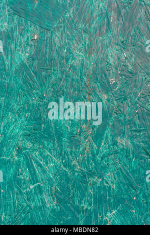 Close-up of the brushstrokes of a piece of green painted plywood, showing paint texture. - Stock Image