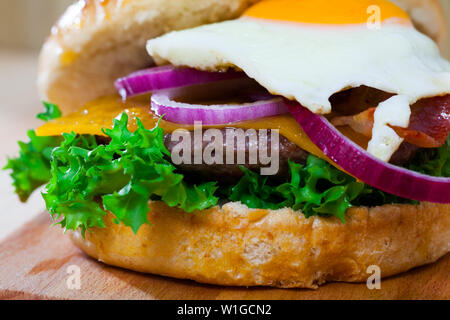 Image of hamburger with beef patty, cheese, fried egg and lettuce - Stock Image
