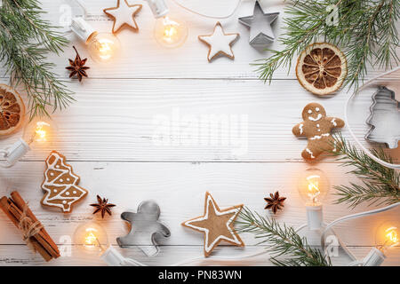 Christmas cookies,fir branch and Christmas lights on wooden table - Stock Image