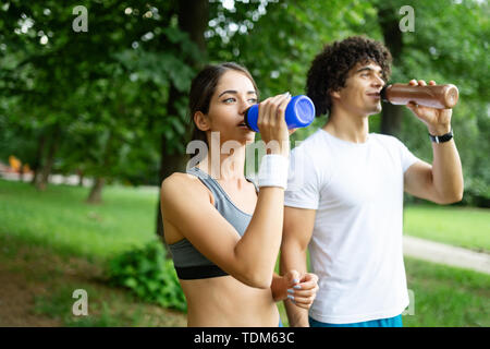 Couple drinks water after jogging to replenish energy and to hydrate - Stock Image