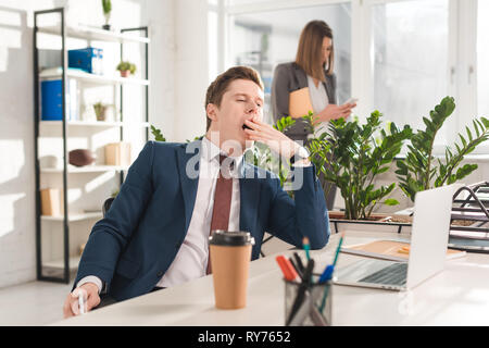 selective focus of tired businessman yawning near female coworker on background - Stock Image